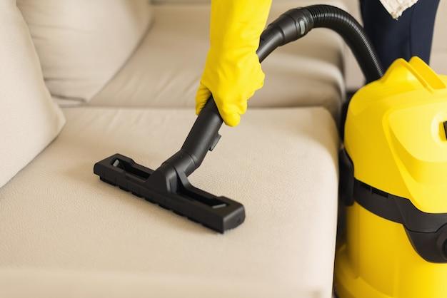 黄色い掃除機でソファを掃除する女性。スペースをコピーします。きれいなコンセプト