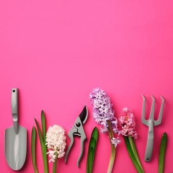 ピンクのパンチの効いたパステル調の背景に花をつける、庭の枝刈り機、熊手。