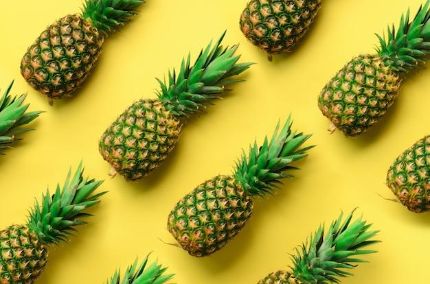 Свежие ананасы на желтом фоне. поп-арт дизайн, креативная концепция. яркий ананасовый узор для минималистичного стиля.