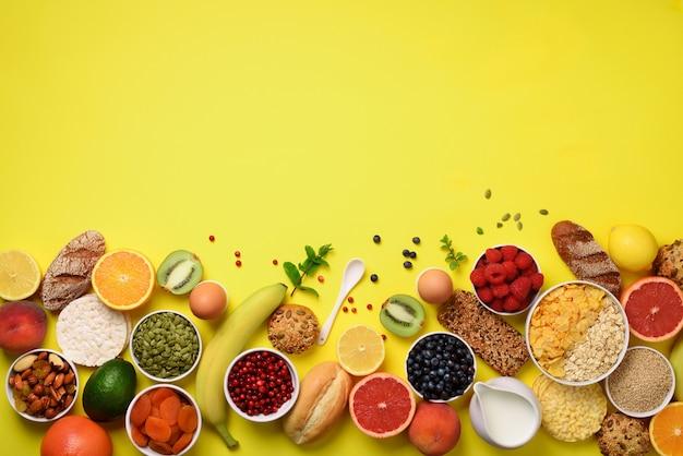 オート麦とコーンフレーク、卵、ナッツ、フルーツ、ベリー、トースト、ミルク、ヨーグルト、オレンジ、バナナ、黄色の背景に桃。