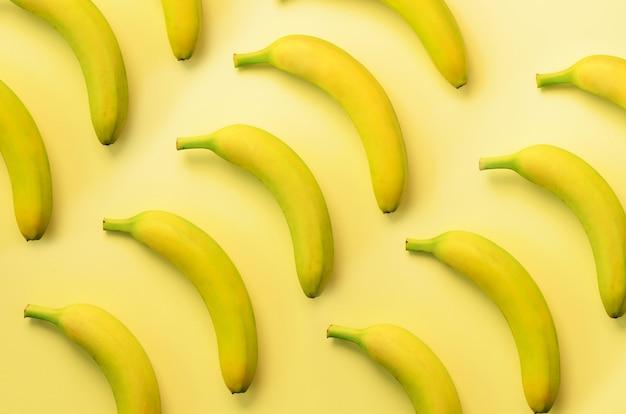 カラフルなフルーツ柄。黄色の背景上のバナナ。ポップアートデザイン、創造的な夏のコンセプト。