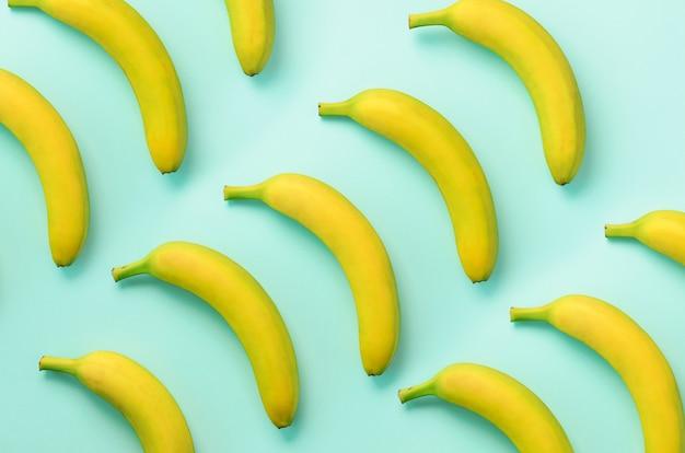 カラフルなフルーツ柄。青い背景上のバナナ。最小限の平置きスタイル。