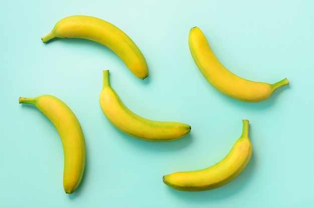 カラフルなフルーツ柄。青い背景上のバナナ。ポップアートデザイン、創造的な夏のコンセプト。最小限の平置きスタイル。