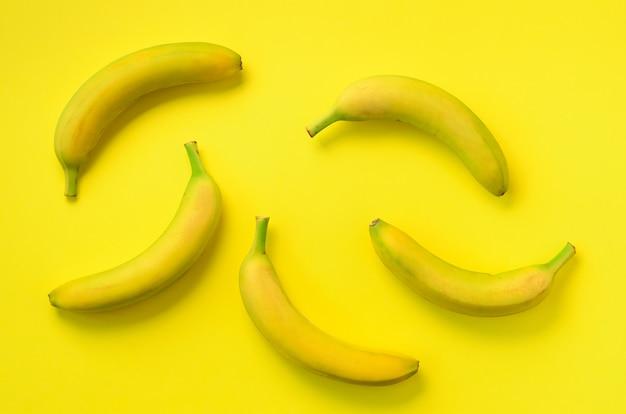 カラフルなフルーツ柄。黄色の背景上のバナナ。上面図。ポップアートデザイン、創造的な夏のコンセプト。最小限の平置きスタイル。