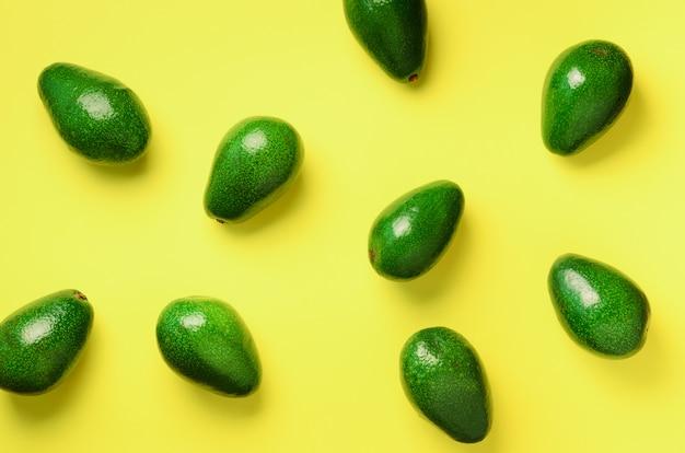 黄色の背景にアボカドパターン。上面図。バナー。ポップアートデザイン、創造的な夏の食べ物のコンセプト。緑のアボカド、最小限のフラットレイアウトスタイル。