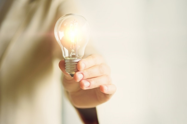Женщина рука лампочку на кремовом фоне. креативная идея, новый бизнес-план, мотивация, инновации, концепция вдохновения.
