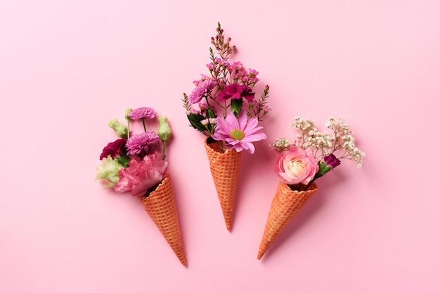 夏の最小限の概念。ピンクの花とパンチの効いたパステル調の背景に葉アイスクリームコーン。