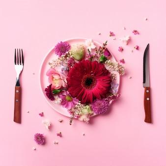 ピンクのプレート、フォーク、パンチの効いたパステル調の背景上のナイフのピンクの花。