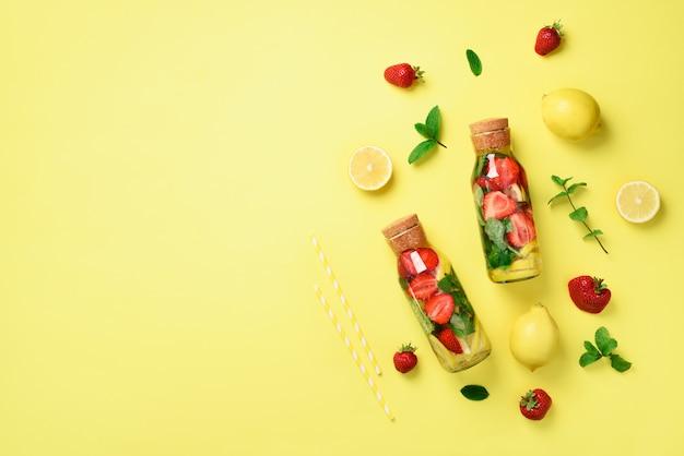 ミント、レモン、イチゴのデトックスウォーターのボトル。柑橘類のレモネード。夏の果物は水を注入しました。