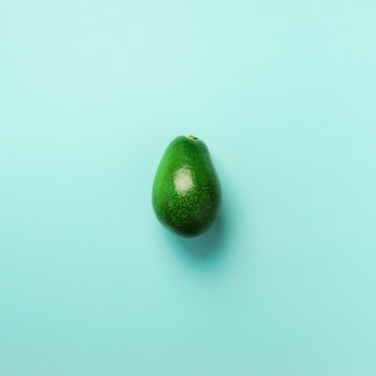 青い背景に緑色のアボカド。上面図。ポップアートデザイン、創造的な夏の食べ物のコンセプト。
