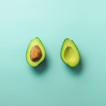 緑のアボカドは青いパステル調の背景に種と半分になります。夏の食べ物のコンセプトです。