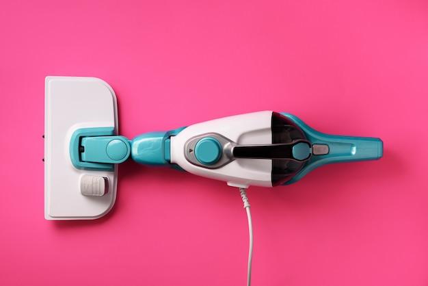 Паровой очиститель шваброй на розовом фоне. концепция уборки