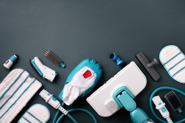 Комплект современных профессиональных пароочистителей на сером фоне.