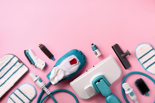 Комплект современных профессиональных пароочистителей на розовом фоне.