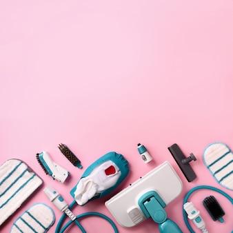 Набор современных профессиональных пароочистителей на розовом фоне.