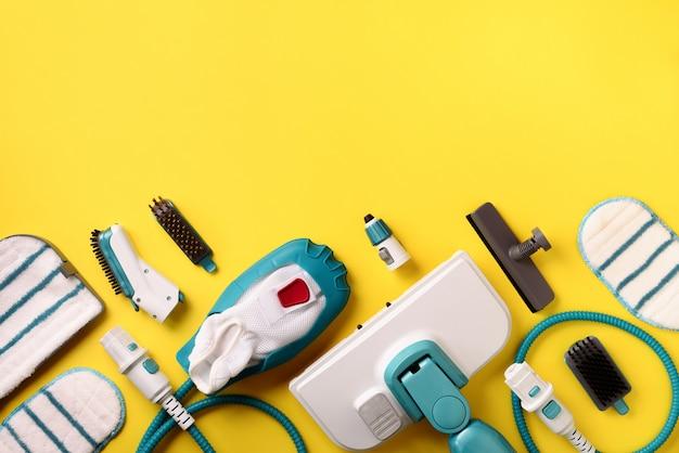 Набор современных профессиональных пароочистителей на желтом фоне.