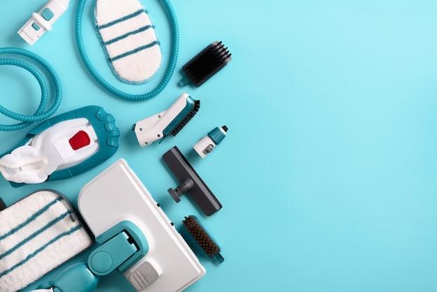 Комплект современных профессиональных пароочистителей на синем фоне.