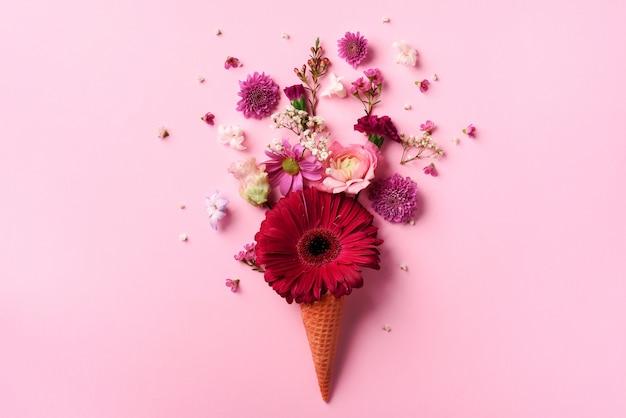 夏の最小限の概念。ピンクの花とパンチの効いたパステル調の背景に葉のアイスクリームコーン。