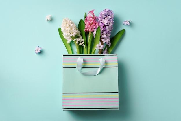 青いパンチの効いたパステル調の背景に買い物袋に新鮮なヒヤシンスの花。クリエイティブなレイアウト