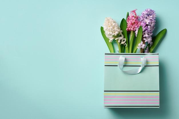 青いパンチの効いたパステル調の背景に買い物袋に新鮮なヒヤシンスの花。
