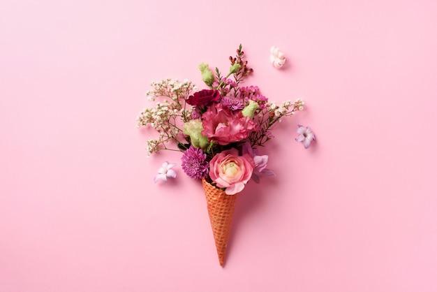 ピンクの花とパンチの効いたパステル調の背景に葉のアイスクリームコーン。