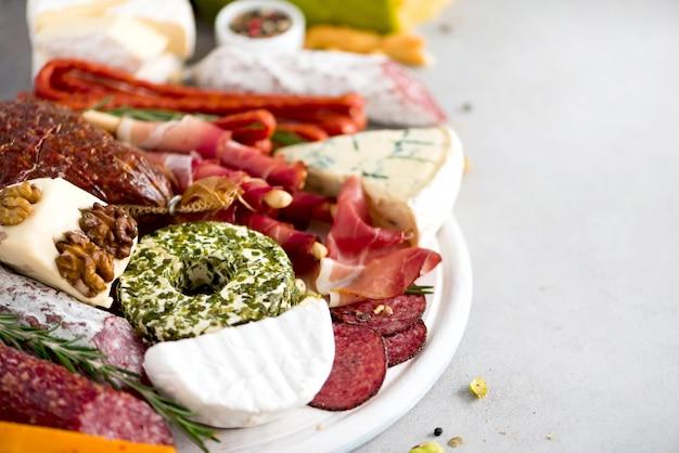 サラミ、冷たいスモークミート、生ハム、ハム、チーズのカッティングボード