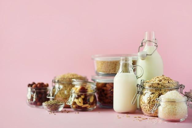 Веганский заменитель молочного молока. стеклянные бутылки с немолочным молоком и ингредиенты на розовом фоне с копией пространства.