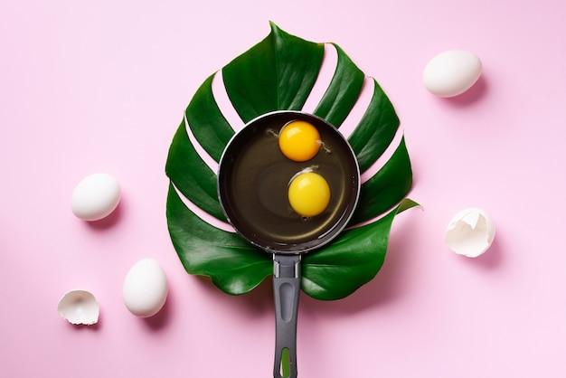 ピンクの背景にモンステラの葉の上の鍋に卵のクリエイティブレイアウト