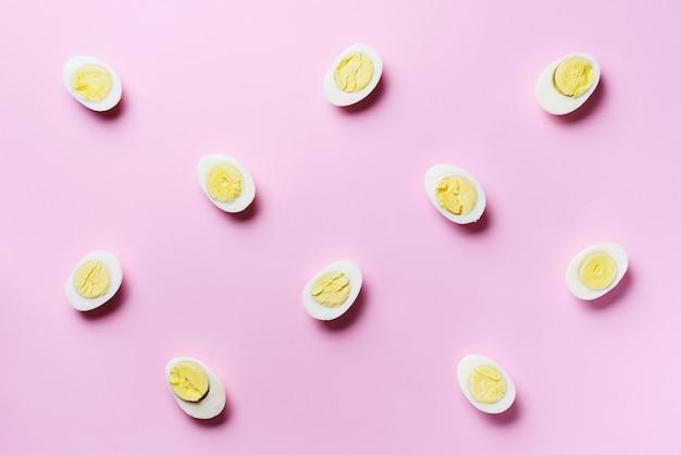 ピンクの背景のゆで卵のパターンを持つ食品のコンセプト