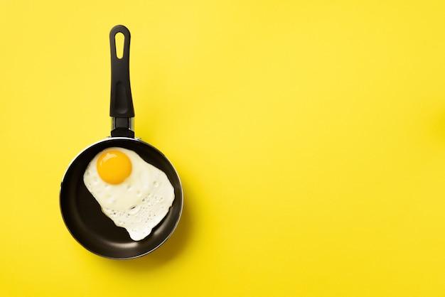 黄色の背景上の鍋に目玉焼き