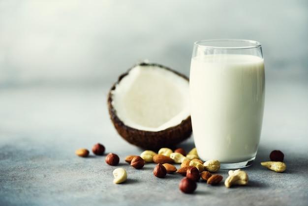 Органическое веганское ореховое молоко в стакане с различным ассортиментом орехов