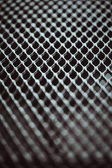 金属の背景。スモールセルグリッドの格子テクスチャ。セレクティブフォーカスポイント。