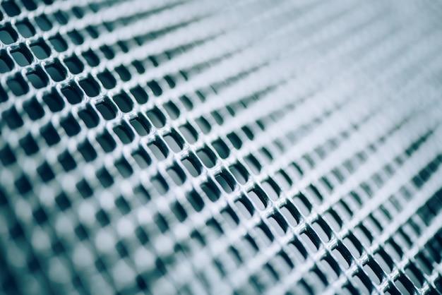 格子状の金属フェンスの表面。ステンレスとアルミニウムの光は、背景をぼかします。マクロテクスチャ