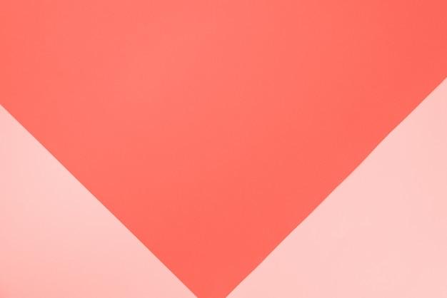サンゴ色の背景。おしゃれなピンクとオレンジ紙。上面図。最小限のコンセプト。