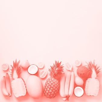 日当たりの良い背景に新鮮な果物。バナナ、ココナッツ、パイナップル、レモン、サンゴ色のメロンとモノクロのコンセプト。上面図。コピースペース。ポップアートデザイン、創造的な夏のデザイン。