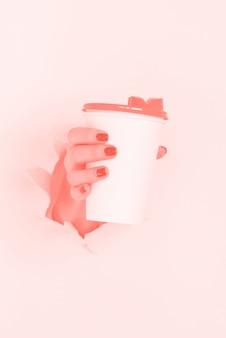 Женская рука держа кружку белой бумаги. забери концепцию кофейной чашки