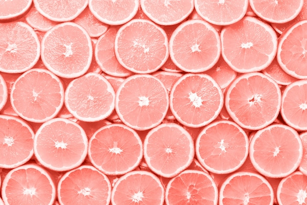 Творческий образец. свежая нарезанная оранжевая фруктовая структура. макрос, вид сверху с копией пространства. пищевая рамка. сочные апельсины в коралловом цветном фоне.