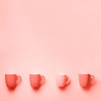 サンゴ色の背景の上のピンクのカップ。上面図