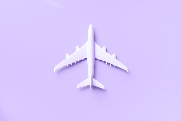 Белый самолет, самолет на модный фиолетовый цвет фона с копией пространства.
