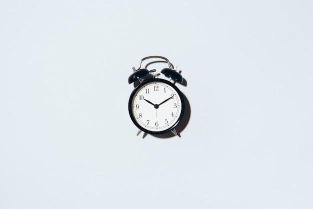 Черный будильник с жесткой тенью на сером фоне.
