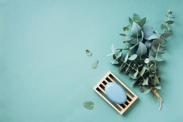 ユーカリのエッセンシャルオイルと緑の背景の石鹸。無駄のない、自然なオーガニックのバスルームツール。