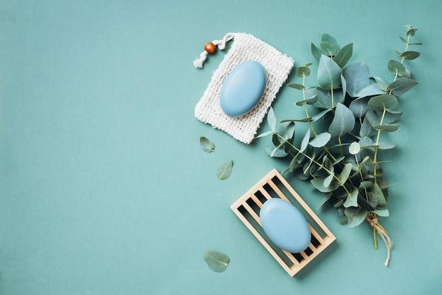木製石鹸皿、石鹸、緑の背景の上のユーカリ。無駄のない、自然なオーガニックのバスルームツール。