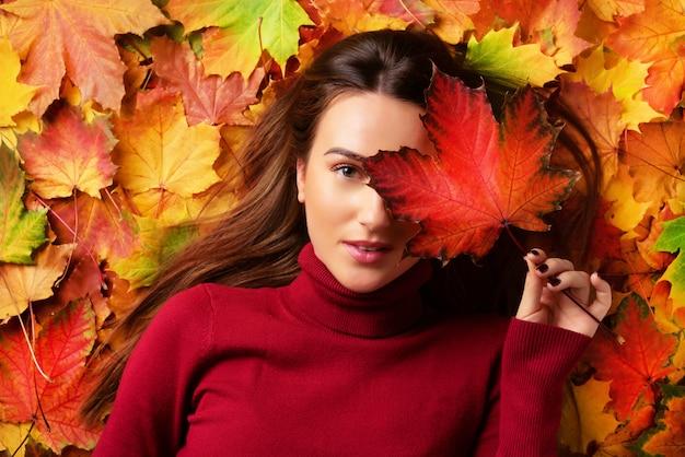 カラフルな落ち葉の背景に赤いカエデの葉を手で保持している女の子。ゴールドの居心地の良い秋のコンセプト。