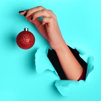 ピンクの背景に赤のきらびやかなクリスマスボールを手で保持している女性