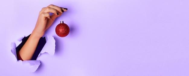 紫色の背景に赤のきらびやかなクリスマスボールを手で保持している女性