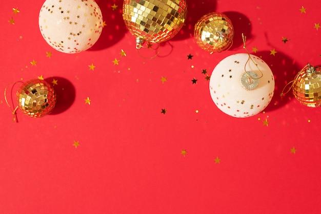 赤の背景に光沢のある星と黄金と白のクリスマスボール