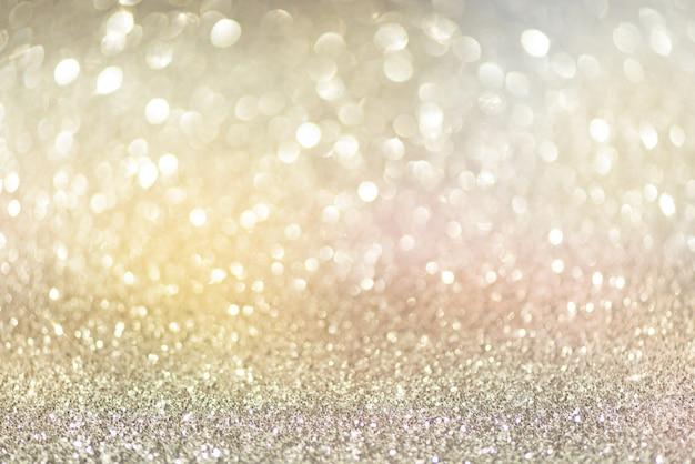 金と銀の抽象的なボケ味が点灯します。コピースペースと光沢のあるキラキラの背景。