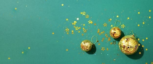 緑の背景に光沢のある星と黄金のクリスマスボール