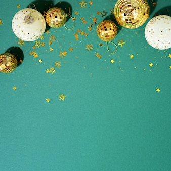 緑の背景に光沢のある星と黄金と白のクリスマスボール