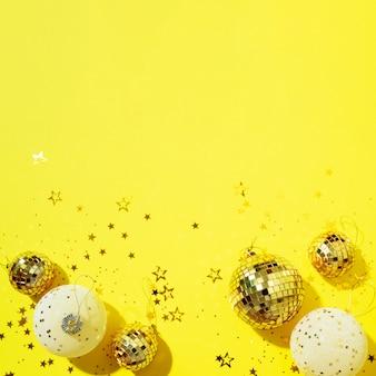 黄色の背景に光沢のある星と黄金と白のクリスマスボール